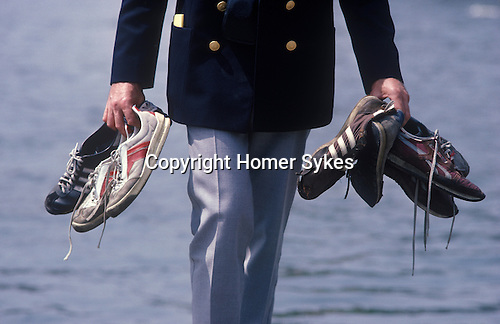 Henley Regatta, Henley on Thames, Oxfordshire, England. Coach holding training shoes.