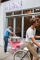 Andr&eacute; Saraiva makes cotton candy in front of the new Cafe Henri in Chinatown. At right, the cafe's interior designer Brett Robinson.<br /> <br /> Danny Ghitis for The New York Times