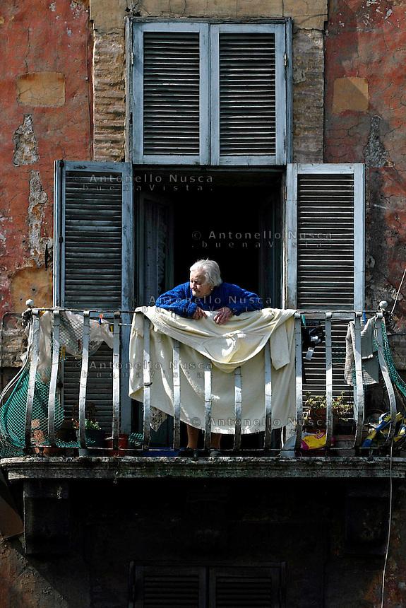 Una anziana signora si affaccia dal balcone della sua casa nel centro storico di Roma. An old woman at her home in Trastevere