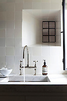 Glazed ceramic tiles cover the bathroom wall with a marble surround to the wash basin
