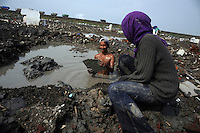 28 year old Bambang and his 23 year old wife Tuti scavenge for bricks, ceramic tiles and any items of value from their former home in the wreckage of Kedung Bendoh village. Trucks cresting the top of the earthen dam holding back the mud can be seen behind them. Since May 2006, more than 10,000 people in the Porong subdistrict of Sidoarjo have been displaced by hot mud flowing from a natural gas well that was being drilled by the oil company Lapindo Brantas. The torrent of mud - up to 125,000 cubic metres per day - continued to flow three years later.