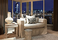 A contemporary armchair against the floor to ceiling windows of the living room with an evening backdrop of Chelsea Harbour