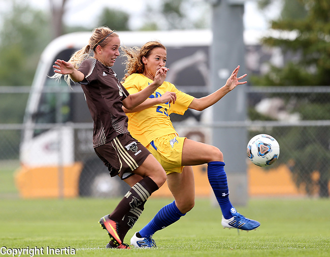 BROOKINGS, SD - AUGUST 13: Annie Williams #23 from South Dakota State chips the ball past Rebecca Martin #6 from Manitoba during the first half of their exhibition match Sunday afternoon at Fishback Soccer Park in Brookings. (Photo by Dave Eggen/Inertia)