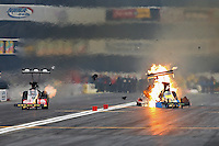Feb 9, 2014; Pomona, CA, USA; NHRA top fuel dragster driver Sidnei Frigo explodes an engine and blows a tire alongside Doug Kalitta during qualifying for the Winternationals at Auto Club Raceway at Pomona. Mandatory Credit: Mark J. Rebilas-