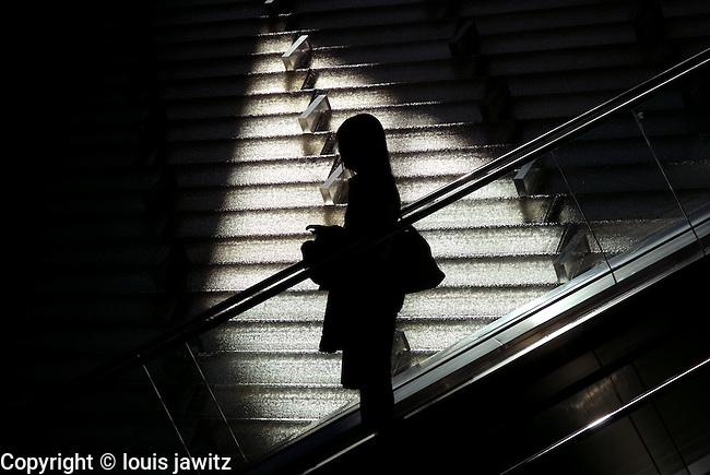 escalator lady worker going down escalator female worker  in silhouette