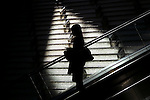 escalator lady worker going down escalator female worker  in silhouette