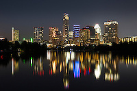 The glimmering Austin Skyline sparkles with a mirror reflection on Lady Bird Lake at night with a view from the Boardwalk Trail in downtown Austin, Texas.
