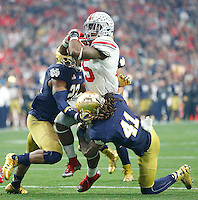 Ohio State Buckeyes running back Ezekiel Elliott (15) squeezes past Notre Dame Fighting Irish cornerback Matthias Farley (41) and Notre Dame Fighting Irish safety Elijah Shumate (22) in the first half at University of Phoenix Stadium in Glendale, AZ on January 1, 2016.  (Chris Russell/Dispatch Photo)