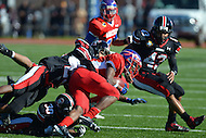 November 22, 2012  (Washington, DC)  Anacostia's Laquan Barber (4) is tackled by Dunbar DB Carlos Atkinson (7) and Davon Fuller (not pictured) during the 2012 DCIAA Turkey Bowl. Dunbar defeated Anacostia 12-8.  (Photo by Don Baxter/Media Images International)
