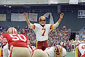 Washington, D.C. - January 8, 1984 -- Washington Redskins quarterback Joe Theismann (7) asks the crowd for silence as he calls signals in the NFC Championship game against the San Francisco 49ers at RFK Stadium in Washington, D.C. on Sunday, January 8, 1984.  San Francisco 49ers left inside linebacker Riki Ellison (50) is pictured a left. The Redskins won the game 24 - 21 to advance to Super Bowl XVIII.  <br /> Credit: Howard L. Sachs / CNP