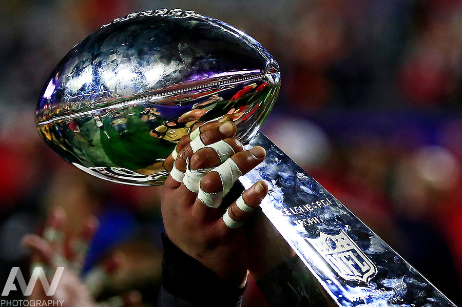 Feb 1, 2015; Glendale, AZ, USA; A member of the New England Patriots hoists the Vince Lombardi Trophy after defeating the Seattle Seahawks in Super Bowl XLIX at University of Phoenix Stadium. Mandatory Credit: Andrew Weber-USA TODAY Sports