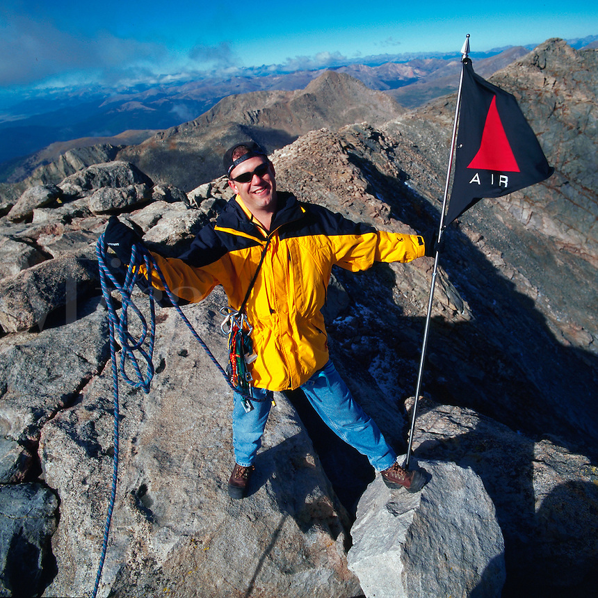 Smiling male hiker with a hiking rope and flag at the summit of Mt. Evans. Colorado.