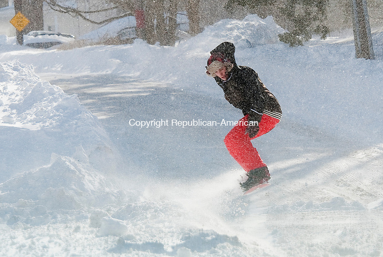 WINSTED, CT 09 FEBRUARY 2013- 020813JS03--Jesse Keslow of Winsted, took advantage of the heavy snow that fell through the region to snowboard down Bridge Street in Winsted on Saturday. .Jim Shannon Republican American.