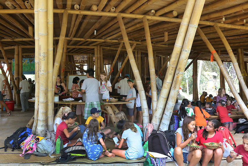 Students meeting for lunch in the Heart of School for a great selection of organic food<br /><br />The Green School (Bali) is one of a kind in Indonesia. It is a private, kindergarten to secondary International school located along the Ayung River near Ubud, Bali, Indonesia. The school buildings are of ecologically-sustainable design made primarily of bamboo, also using local grass and mud walls. There are over 600 students coming from over 40 countries with a percentage of scholarships for local Indonesian students.<br /><br />The impressive three-domed &quot;Heart of School Building&quot; is 60 metres long and uses 2500 bamboo poles. The school also utilizes renewable building materials for some of its other needs, and almost everything, even the desks, chairs, some of the clothes and football goal posts are made of bamboo.<br /><br />The educational focus is on ecological sustainability. Subjects taught include English, mathematics and science, including ecology, the environment and sustainability, as well as the creative arts, global perspectives and environmental management. This educational establishment is unlike other international schools in Indonesia. <br /><br />Renewable energy sources, including solar power and hydroelectric vortex, provide over 50% of the energy needs of the school. The school has an organic permaculture system and prepares students to become stewards of the environment. <br /><br />The school was founded by John and Cynthia Hardy in 2008.