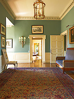 The hallway as been painted an historical green and is furnished with a 20th century sofa