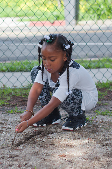 Berkeley CA Kindergarten student, African American, playing at making sand patterns, independently, during school recess