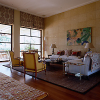 Two large comfortable sofas heaped with cushions and a pair of matching armchairs are grouped round a low coffee table creating a welcoming seating area