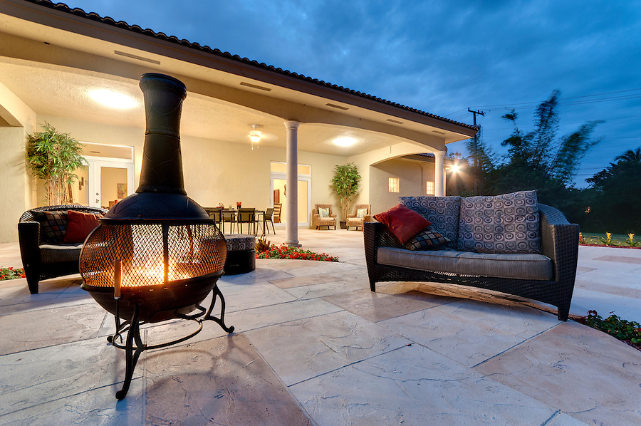 Fire pit in a modern backyard with patio furniture.