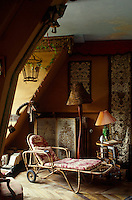 A bamboo chaise-longue covered in faded toile de Jouy in a corner of the attic living room which is hung with antique textiles