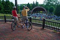 A couple riding their bicycles watch   and listen to an outdoor concert at the ampitheater in Alum Creek Park in Westerville as part of a summer concert series.