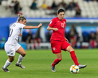 GRENOBLE, FRANCE - JUNE 15: Christine Sinclair #12 of the Canadian National Team passes the ball as Annalie Longo #10 of the New Zealand National Team pressures during a game between New Zealand and Canada at Stade des Alpes on June 15, 2019 in Grenoble, France.