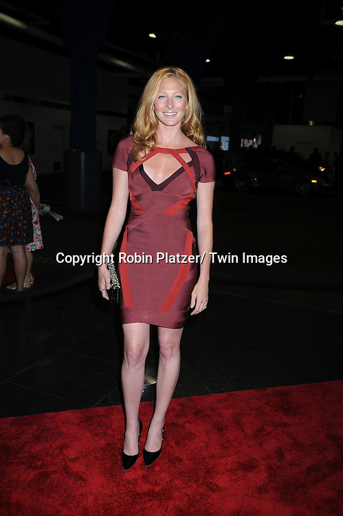 Maggie Rizer in Herve Leger maroon dress posing for photographers at The Fresh Air Fund's Salute to American Heroes Gala on June 3, 2010 at Pier Sixty at Chelsea Piers in New YOrk City.