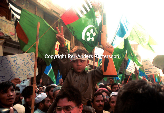 A boy with a toy rifle on his fathers shoulders at a pro-Taliabn demonstration on September 28, 2001 in the old town in Peshawar, Pakistan. A big demonstration was held after the Friday prayer supporting of Osama Bin Laden and the Taleban movement in Afghanistan..Photo: Per-Anders Pettersson...