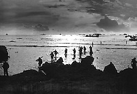 From Coast Guard-manned landing craft, American invaders wade through a golden, shallow surf to hit the beach of Tinian Island.  Units of a mighty task force stand on the horizon - Navy warships, transports and LSTs.  July 1944.  (Coast Guard)<br /> Exact Date Shot Unknown<br /> NARA FILE #:  026-G-2658<br /> WAR &amp; CONFLICT BOOK #:  1170