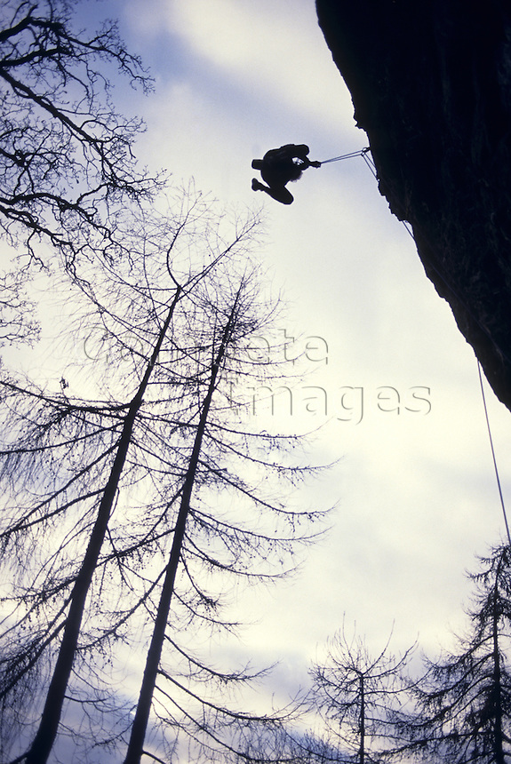 Man abseiling a rock face by trees