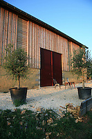The massive steel double doors of a converted barn in the Dordogne, once used for drying tobacco, have been painted a deep burgundy
