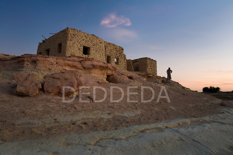 A local Siwan man stands near an abandoned mudbrick village on the outskirts of Siwa Town in the Siwa Oasis, Egypt.