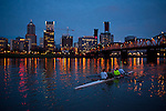 Crew teams working out on the Willamette River in the early morning with downtown Portland Oregon in the background.