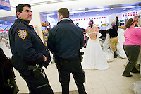 "Two police officers keep an eye open for disorder as brides-to-be try on discounted wedding dresses during the annual ""Running of the Brides"", a a first-come-first-served bridal gown sale, at the Filene's Basement store in New York City, USA, 3 March 2006."