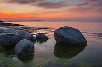 Stenar på en klipphäll vid havet med skymning över Stockholms skärgård.