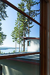 A window looks out to the Salish Sea across the metal roof of a contemporary home.