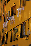 The wash is hanging out  the window to  dry in the natural way in some streets of Florence Italy.