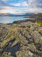County Galway, Ireland:  Afternoon light on the rocky shoreline of Rinvyle Point in the Connemara Region with Mweelrea Mountains in the distance