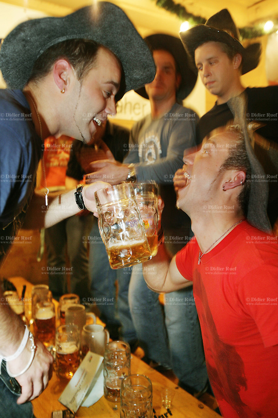 Switzerland. Canton Zürich. Winterthur. Oktoberfest. Bier fair. Cheers, Your health. Two young men are shaking their beer mugs. The portrait of Ernesto Che Guevara is printed the red t-shirt. Night life. © 2006 Didier Ruef