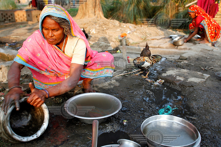 A woman washes pots and plates near her home.