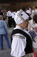 Woman dressed in the traditional Moravian costume, having a taste of the local wine while listening to the music being played under Charles Bridge in Prague, during the ride of the Kings.<br /> <br /> Twelve-year-old Frantisek Libosvar dressed as a girl and with a rose in his mouth leads the royal procession during Ride of the Kings as part of Navalis Celebrations on May 15, 2015 in Prague, Czech Republic. The Navalis Saint John's celebrations take place to commemorate Czech saint and Prague native, Saint John of Nepomuk, patron of all people of the water. <br /> <br /> <br /> The Ride of the Kings takes place during the spring, as a part of the Pentecost traditions . A group of young men ride through a Prague in a ceremonial procession. The ride is headed by chanters, followed by pageboys with unsheathed sabres who guard the King &ndash; a young boy with his face partially covered, holding a rose in his mouth &ndash; and the rest of the royal cavalcade. The King and pageboys are dressed in women&rsquo;s ceremonial costumes, while the other riders are dressed as men. The entourage rides on decorated horses, stopping to chant short rhymes that comment humorously on the character and conduct of spectators. The chanters receive donations for their performance, placed either in a money box or directly into the riders&rsquo; boots. The King&rsquo;s retinue returns home after a few hours of riding, and celebrates in the evening at the house of the King with a small feast, music and dancing. The practices and responsibilities of the Ride of the Kings are transmitted from generation to generation. The traditional paper decorations for the horses and the ceremonial costumes, in particular, are made by women and girls familiar with the processes, colour patterns and shapes specific to each village.