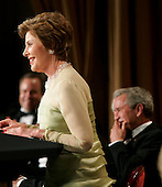 First lady Laura Bush stole the show during the annual White House Correspondents' Association dinner when she took over the President's speech and made the crowd, including husband, U.S. President George W. Bush, seen behind, erupt in laughter at the Washington Hilton in Washington, D.C., Saturday 30 April 2005. The annual dinner began in 1914 as a bridge between the White House and its media corps and tonight feautured a mix of political insiders including Supreme Court Justices, Antonin Scalia and Stephen Breyer, and Hollywood elite such as Goldie Hawn and Richard Gere. <br /> Credit: Katie Falkenberg - Pool via CNP