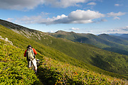 A hiker descending the Jewell Trail in Thompson and Meserve's Purchase in the White Mountains, New Hampshire during the summer months. The Jewell Trail is named for Sergeant Winfield S. Jewell. He was an Army Signal Corps observer on Mount Washington from 1878-1880. And on April 12, 1884, while on the Greely expedition to the Arctic, Jewell died of starvation. Out of the 25 men on the three year Greeley expedition (1881–1884), only six survived.