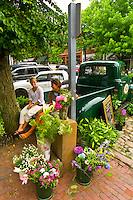 Two girls selling plants from the back of an old pickup truck on the cobblestone streets of Nantucket town, Nantucket island, Massachusetts, USA