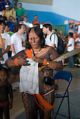 Altamira, Brazil. Encontro Xingu protest meeting about the proposed Belo Monte hydroeletric dam and other dams on the Xingu river and its tributaries. A Kayapo woman tying a piece of Paulo Fernando Vieira Souto Rezende, the Eletrobras representative's shirt onto her machete.