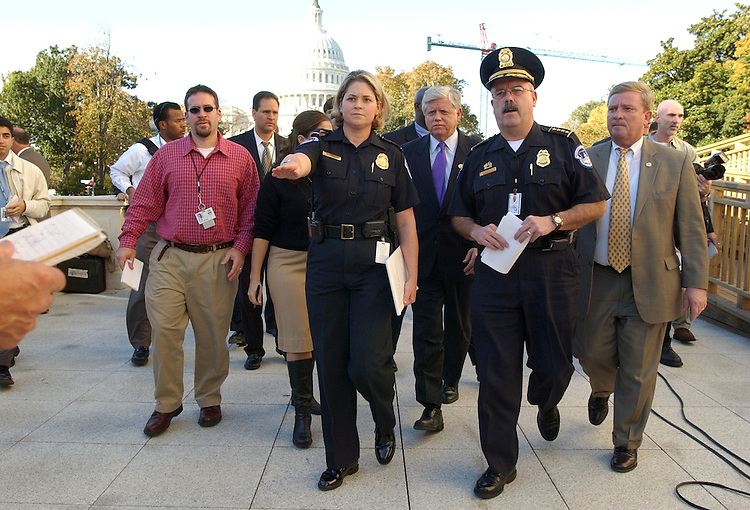 Off. Jessica Gissuvel of Capitol Police and Chief Terrance Gainer, walk to a news conference after the search for a gun in Cannon Building turned out to be a toy for a Halloween costume.