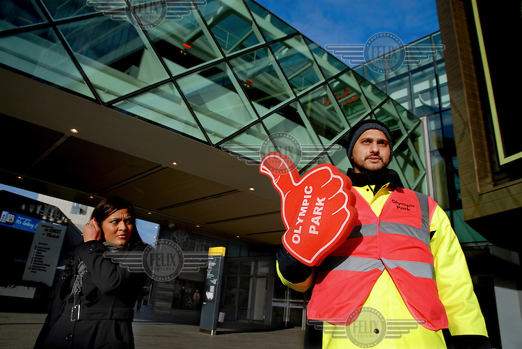 A man with large signes fixed to his hands which read 'Olympic Park' points the way toward the Olympic park from the Westfield Stratford City shopping mall, the largest mall in Europe, East London. ..