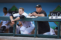 Chicago White Sox Player Development Assistant Tommy Thompson (right) watches the action from the dugout with center fielder Adam Engel (11) during the game against the Rochester Red Wings at BB&T BallPark on May 14, 2019 in Charlotte, North Carolina. The Knights defeated the Red Wings 13-7. (Brian Westerholt/Four Seam Images)