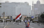 A pro-regime supporter holds Egyptian national flags in front of army vehicles positioned on Cairo's Tahrir square during a demonstration against a recent court's decision to drop a murder charge against the former president, on December 5, 2014, on Abdel Moneim Riad Square in the capital Cairo. A Cairo court on November 29, 2014, dropped murder and corruption charges against Mubarak and seven aides in a case involving the deaths of some of the roughly 800 demonstrators killed in the 2011 revolt. Photo by Amr Sayed