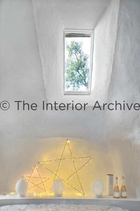 Illuminated stars decorate a shelf beneath this narrow window