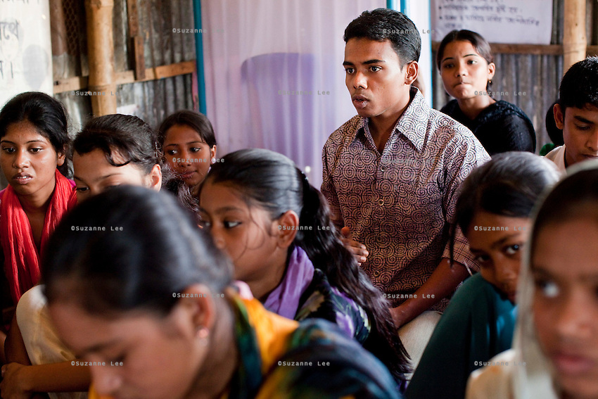 """Jewel Mahammud Kawsan (17, center right) speaks during a monthly meeting of a Children's Group in Bhashantek Basti (Slum) in Zon H, Dhaka, Bangladesh on 23rd September 2011. When asked if an abused wife could return to her family, Jewel says, """"Society doesn't take it well. It is not accepted if she leaves the husband's house. Even (her own parents) will tell her to be accommodative even if her husband beats her, because after marriage, that is now her real address."""" Jewel also tells a true story of a girl who used to be a member of the children's group. When she turned 14/15, her parents wanted to marry her off. The children's group went to village elders to counsel the family and the marriage was stopped. The children felt proud but sadly, after 2 months, she was quietly married off. Now, at 18, she is a mother of a girl child and is not happy in the marriage. Her husband is also a young boy but is violent in nature and beats her. She is tied to motherhood and house chores and not allowed to join the other children. The families are also fighting because of dowry related issues."""" The Bhashantek Basti Childrens Group is run by children for children with the facilitation of PLAN Bangladesh and other partner NGOs. Slum children from ages 8 to 17 run the group within their own communities to protect vulnerable children from child related issues such as child marriage. Photo by Suzanne Lee for The Guardian"""